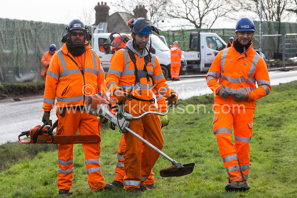Harefield, UK. 8 February, 2020. HS2 engineers carry a chainsaw and strimmer in order to carry out tree felling works for the high-speed rail project. The activists were successful in preventing any of the scheduled tree felling by HS2 and after an intervention by a police officer all tree felling and strimming work has now been cancelled for the weekend.