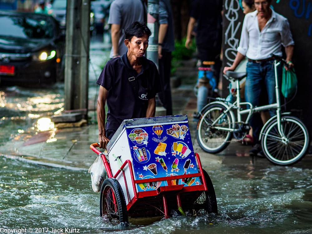 27 MAY 2017 - BANGKOK, THAILAND: An ice cream vendor pushes his cart along a sidewalk flooded by monsoonal rains on Ekkamai Road in suburban Bangkok. The rainy season in Bangkok usually starts in mid-June but started almost a month early this year. There have been daily thunderstorms and localized flooding throughout central Thailand since the middle of May.     PHOTO BY JACK KURTZ