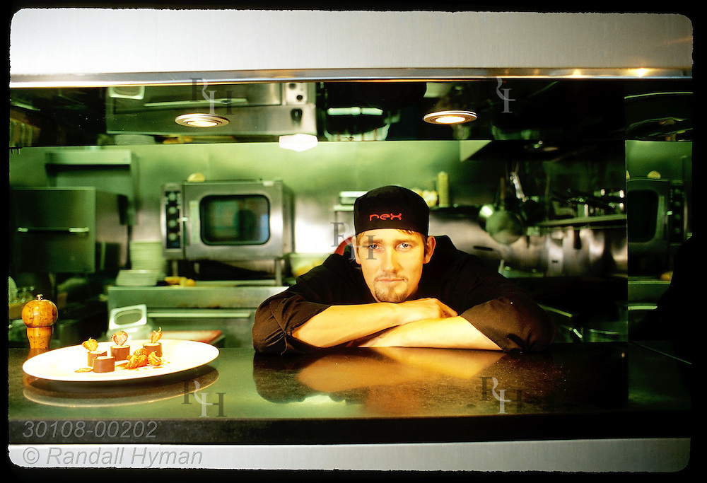 Chef Hallgrimur Ingi Thorlaksson of the futuristic-looking restaurant Rex Bar poses by kitchen serving window; Reykjavik, Iceland