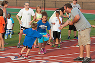 Middletown, New York - A young boy crosses the finish line in a race during the Twilight Track and Field Series run by the Middletown High School Varsity track program on July 22, 2014.