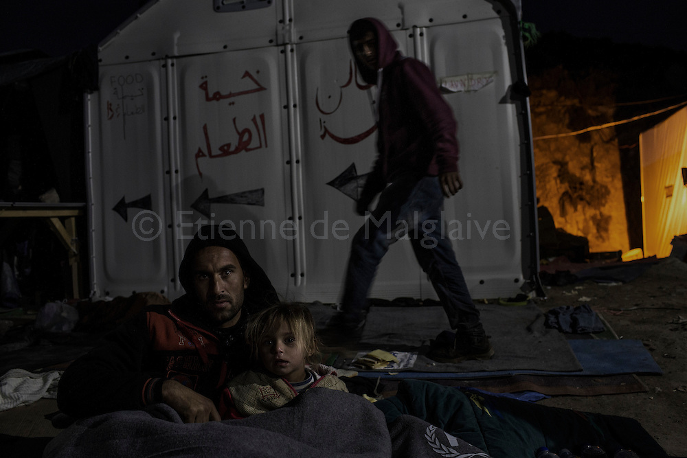 A man and his young daughter refugees from Afghanistan settle for spending the night inside the Mithimna transit camp  near Molivos, Greece on 07<br /> November, 2015. Lesbos, the Greek vacation island in the Aegean Sea between Turkey and Greece, faces massive refugee flows from the Middle East countries.