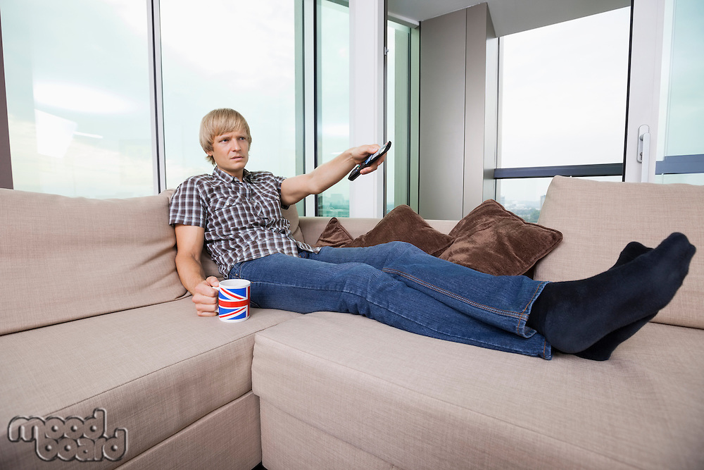 Relaxed mid-adult man watching television while having coffee on sofa at home