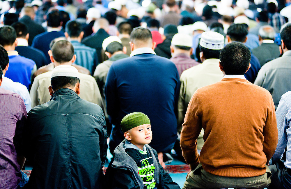 London, UK - 20 July 2012: a child watches in camera while a crowd of faithful prays in the East London Mosque during the first day of Ramadan.