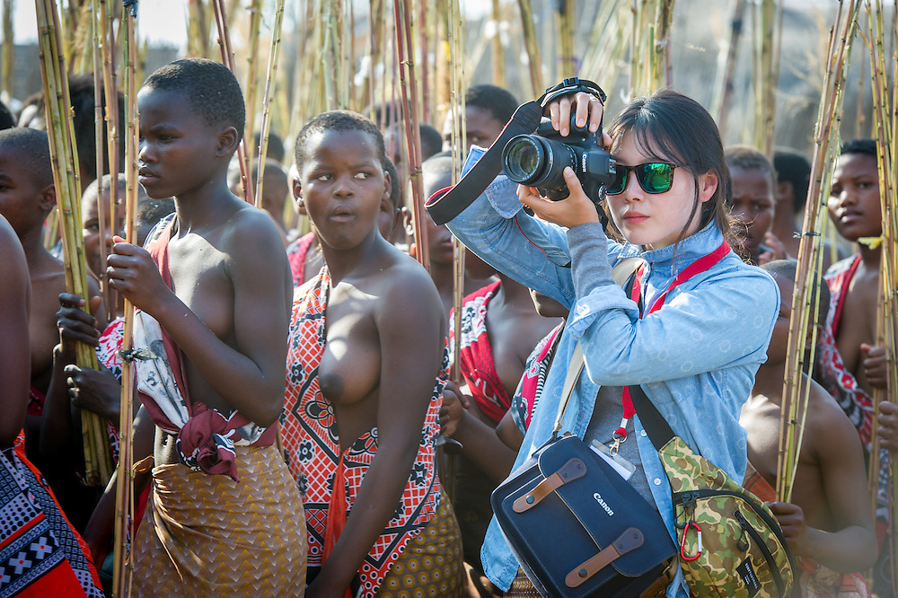 Asian tourist photographing the Reed Dance-Ludzidzini, Swaziland, Africa - Tourist photographing the Swazi Umhlanga, or reed dance ceremony, 100,000 unmarried women , or maidens, celebrate their virginity by bringing reeds for the Swazi Queen Mother's Kraal during this 8 day long annual tradition and dancing in a massive gathering before King Mswati III, the royal family, and the public.