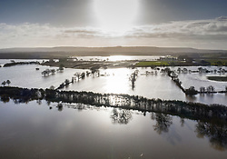 © Licensed to London News Pictures. 21/12/2019. Pulborough, UK. The sun briefly shines on to flood water filled fields south of Pulborough, West Sussex after the River Arun burst its banks and flooded local businesses and farm land. River levels remain high after heavy overnight rain in the south where more rain is expected today. Photo credit: Peter Macdiarmid/LNP