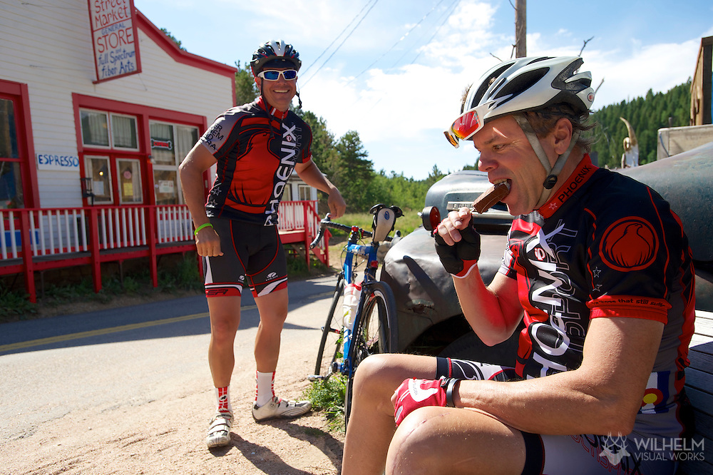 08 September 2013: Rick Jacquemard of Boulder (right) enjoys a frozen chocolate ice cream from the Utica Street Market in Ward at the top of the climb while teammate Damon Devincenzi looks on during the bicycle ride from the front range city of Boulder to the mountain town of Ward via Old Stage Road and Left Hand Canyon in Boulder, CO. ©Brett Wilhelm/Clarkson Creative - RAW Files Available On Request