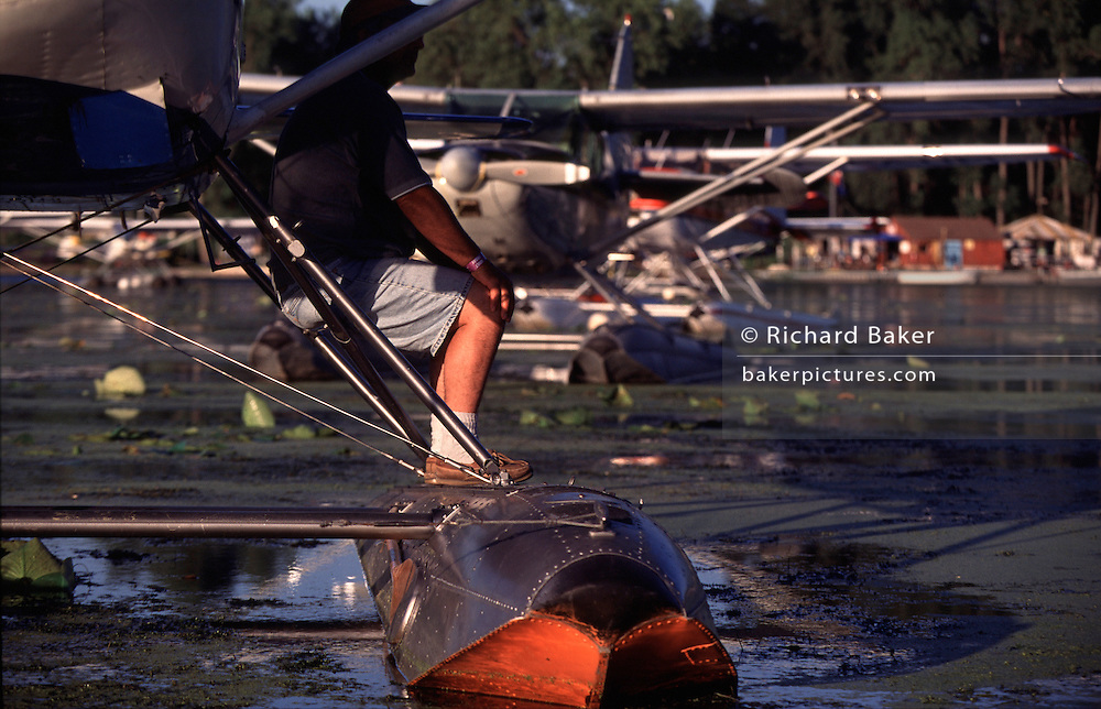 An aviator sits on a float of his aircraft in a parking lake for seaplanes during the world's largest aviation airshow at Oshkosh, Wisconsin, at Oshkosh Air Venture, the world's largest air show in Wisconsin USA. Close to a million populate the mass fly-in over the week, a pilgrimage worshipping all aspects of flight. The event annually generates $85 million in revenue over a 25 mile radius from Oshkosh. The event is presented by the Experimental Aircraft Association (EAA), a national/international organization based in Oshkosh. The airshow is seven days long and typically begins on the last Monday in July. The airport's control tower is the busiest control tower in the world during the gathering.