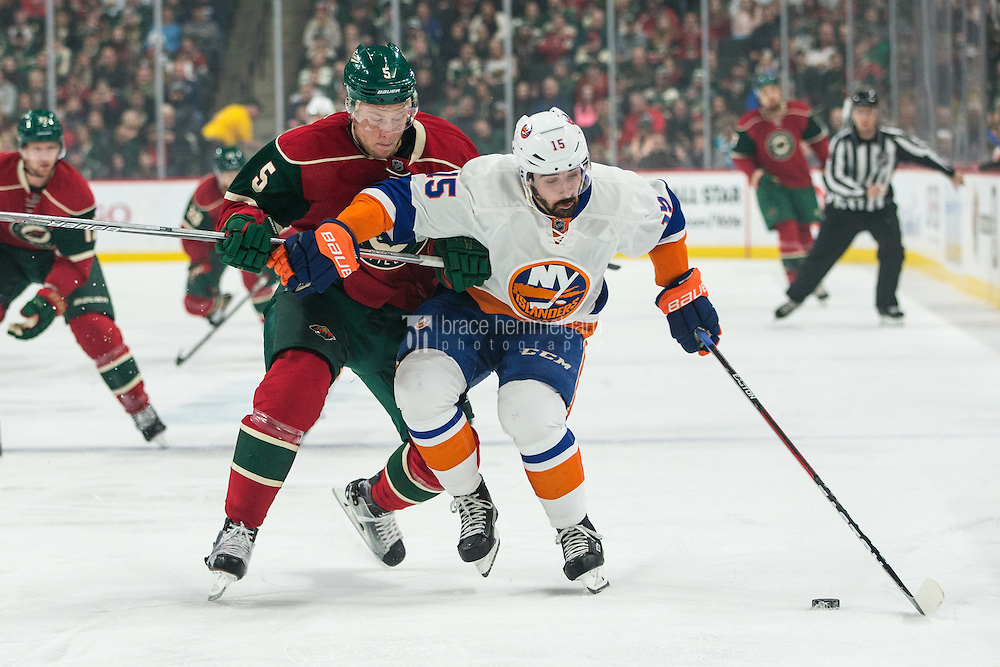 Dec 29, 2016; Saint Paul, MN, USA; Minnesota Wild defenseman Christian Folin (5) hits New York Islanders forward Cal Clutterbuck (15) during the first period at Xcel Energy Center. Mandatory Credit: Brace Hemmelgarn-USA TODAY Sports