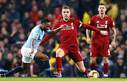 Manchester City's Raheem Sterling (left) and Liverpool's Jordan Henderson battle for the ball during the Premier League match at the Etihad Stadium, Manchester.