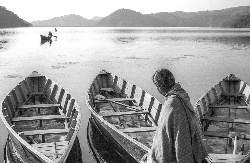 A Nepali woman watches the return of boats from the opposite shore of Phewa Lake, Pokhara Valley, Nepal.