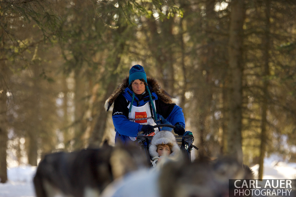 March 7th, 2009:  Anchorage, Alaska - Cindy Gallea from Seeley Lake, Montana heads through the Behm Lake woods during the 2009 Iditarod Ceremonial Start.