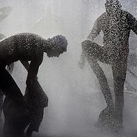 Nederland.Almere Haven.27 augustus 2005.<br /> Na het 1e onderdeel van de Holland Triathlon, de 4 km afstandzwemmen in het IJsselmeer rennen de deelnemende atleten uit het water door de douche naar het volgende onderdeel het wielerrennen.<br /> op de foto staat een deelnemer onder de buitendouche snel zijn wetsuit  uit te trekken alvorens verder te rennen.<br /> Sport.AtleetAtletiek..afkoelen.Verfrissen.Water.Afspoelen.zwemmen.<br /> Participants in the Holland Triathlon 2005.