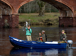 Pictured: adventurer Polly Murray sprays champagne to mark the official start of the new season.<br /> <br /> Anglers from all over the country arrived in Kinclaven, Perthshire for the first day of the new salmon fishing season on the River Tay, which is marked with whisky and sees the anglers led to the water by pipers.<br /> <br /> <br /> © Dave Johnston / EEm