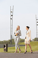 Full length of young businesswomen walking together against clear sky