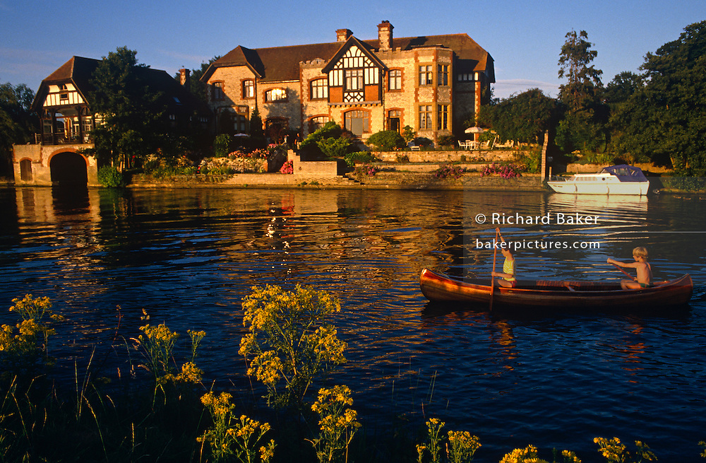 There is golden light across this narrow stretch of river, yellow flowers are on the bank and in late golden sunlight, two boys paddle upstream in their Indian canoe on the River Thames near the village of Shillingford, England. Lazily they plunge their paddles into the calm, clear blue waters of this majestic river whose source rises in deepest Gloucestershire to its industrial estuary in the English Channel 215 miles (346 km) away. But here in Oxfordshire, it is an idyllic scene of innocent childhood on calm rural waters in a beautiful and tranquil setting, on an English summer afternoon. The boys don't appear to be wearing life vests nor safety equipment but propel their craft forwards against the current with confidence.