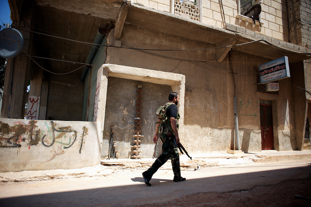 August 09, 2012 - Aleppo, Syria: A Free Syria Army (FSA) fighter leaves the headquarters in Haneno neighborhood, to join his comrades on the frontline at Salehedine...The Syrian army and the FSA have in the past week exchanged heavy fire in a battle for the control of Syria's economic capital, Aleppo. (Paulo Nunes dos Santos/Polaris)