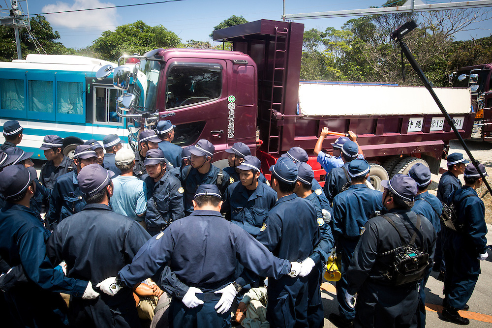OKINAWA, JAPAN - AUGUST 19 : Anti U.S base protesters is seen being guarded by police as the truck pass by after dumping gravels for construction of the road to helipads in front of the gate of U.S. military's Northern Training Area in the village of Higashi, Okinawa Prefecture, on August 19, 2016. Japanese government resume construction of total six helipads in a fragile ten million year old Yanbaru forest that is home to endemic endangered species such as the Okinawan rail and Okinawan wood pecker. (Photo by Richard Atrero de Guzman/NURPhoto)