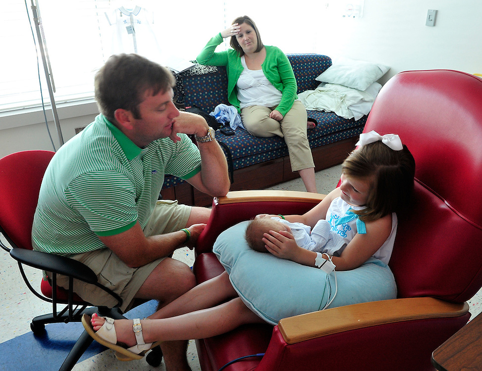 Jessica Kirk, center, has a moment of rest as her daughter, Maddie Grace Kirk, hold's her little brother Samuel under the watchful eyes of her father Kyle Kirk at St. Mary's Hospital on Thursday, May 20, 2010 in Athens, Ga.  The Kirk family lost their second child, Zachary, who was born four months prematurely, seven months after he was born in April of 2009.  .