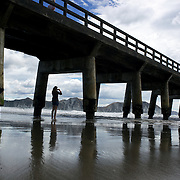The concrete wharf at Tolga Bay North East of Gisborne. Tolaga Bay is both a bay and small town on the East Coast of New Zealand's North Island located 45 kilometres northeast of Gisborne and 30 kilometres south of Tokomaru Bay..The long wharf, the longest in New Zealand at 600m in length, was built to accommodate visiting vessels. In the 1830s there was a thriving flax trade involving early European traders. The wharf is now in threat and a committee from the township are appealing for funds and technical help to restore and save it..Two rivers reach the Pacific Ocean at Tolaga Bay, the Waiau and the Mangaheia. North Island, New Zealand,  19th January 2010. Photo Tim Clayton