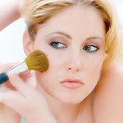 Young woman applying make up.