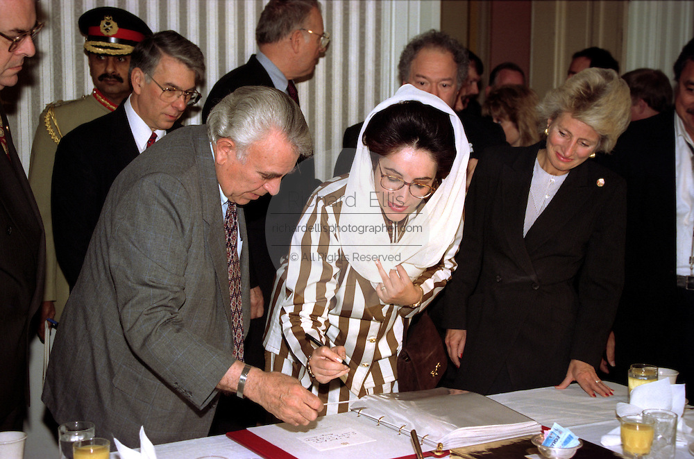 US House International Relations Chairman Ben Gilman with Pakistan Prime Minister Benizar Bhutto as she signs a guest book before a meeting on Capitol Hill April 6, 1995 in Washington, DC.