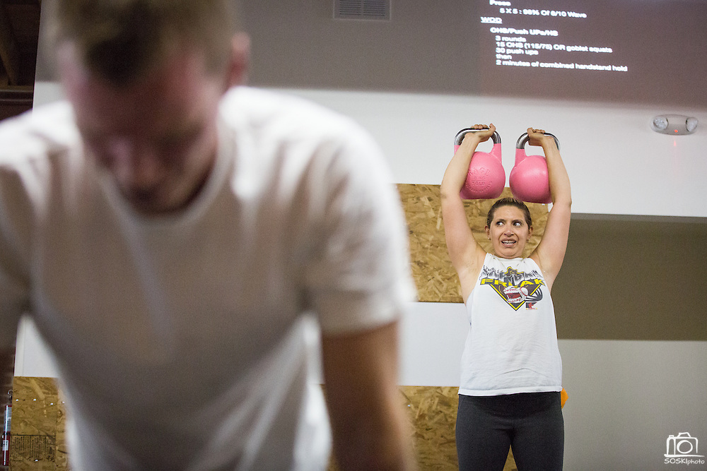 Jenn Flores of San Jose presses kettlebells for two minutes during a CrossFit program at ThirdSpace Fitness in San Jose, California, on July 6, 2015. (Stan Olszewski/SOSKIphoto for Content Magazine)