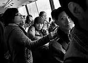 A woman chats on a mobile phone as she rides a public bus in Chongqing.