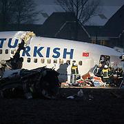 Amsterdam Schiphol Nederland 25 februari 2009 20090225 Foto: David Rozing .Pilots are taken out of cockpit.  Piloten worden geborgen Dead, pilot, pilots, bergen, lijk, body, bodies, casulalty, deadly, burrying, Evening, avond, fireman, firemen..Airplane of Turkish Airlines crashed just 1 kilomtre short of the landing strip of Schiphol Airport. The plane broke in 3 pieces The plane, with 135 passengers on board, crashed short of the runway near the A9 motorway and suffered significant damage. It was Flight 1951 from Istanbul and was a 737-800 aircraft....SCHIPHOL Langs de A9 is woensdagochtend om 10.31 uur tussen het Rotterpolderplein en Schiphol een vliegtuig van Turkish Airlines neergestort. Er zijn negen doden gevallen en vijftig passagiers raakten gewond waarvan 25 ernstig. Het vliegtuig is in drie delen uit elkaar gevallen. Het gaat om een Boeing 737 met 127 passagiers aan boord en zeven bemanningsleden. Het lijkt erop dat het passagiersvliegtuig de Polderbaan net niet heeft kunnen bereiken. Het vliegtuig is aan de andere kant van de A9 in een akker gecrasht. De oorzaak van het ongeluk is nog onbekend. ..Foto: David Rozing