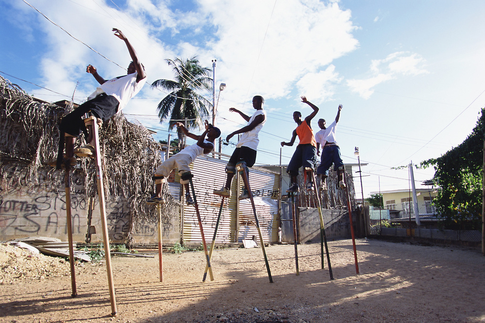 """Trinidad and Tobago """"MOKO JUMBIES: The Dancing Spirits of Trinidad"""".(Students practice Limbo dancing and jumps in the yard. When two students lift one leg towards each other and hold onto it, another child can move below the legs Limbo style. Only experienced Moko Jumbies can perform this difficult dance.).A photo essay about a stilt walking school in Cocorite, Trinidad..Dragon Glen de Souza founded the Keylemanjahro School of Art & Culture in 1986. The main purpose of the school is to keep children off the streets and away from drugs..He first taught dances like the Calypso, African dance and the jig with his former partner Cathy Ann Samuel.  Searching for other activities to engage the children in, he rediscovered the art of stilt-walking, a tradition known in West Africa as the Moko Jumbies , protectors of the villages and participants in religious ceremonies. The art was brought to Trinidad by the slave trade and soon forgotten..Today Dragon's school has over 100 members from age 4 and up..His 2 year old son Mutawakkil is probably the youngest Moko Jumbie ever. The stilts are made by Dragon and his students and can be as high as 12-15 feet. The children show their artistic talents mostly at the annual Carnival, which today is unthinkable without the presence of the Moko Jumbies. A band can have up to 80 children on stilts and they have won many of the prestigious prizes and trophies that are awarded by the National Carnival Commission. Designers like  Peter Minshall , Brian Mac Farlane and Laura Anderson Barbata create dazzling costumes for the school which are admired by thousands of  spectators. Besides stilt-walking the children learn the limbo dance, drumming, fire blowing and how to ride  unicycles..The school is situated in Cocorite, a suburb of Port of Spain, the capital of Trinidad and Tobago..all images © Stefan Falke"""