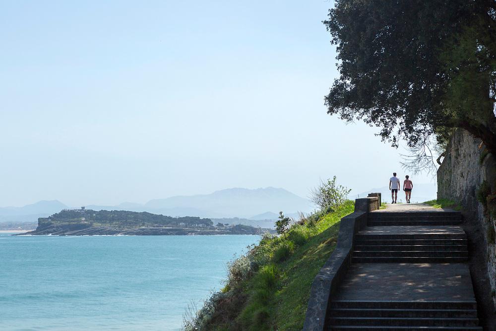 SANTANDER, SPAIN - April 19 2018 - Couple walking along Santander Coastal Footpath with view of Magdalena Peninsula, Cantabria, Northern Spain, Europe.