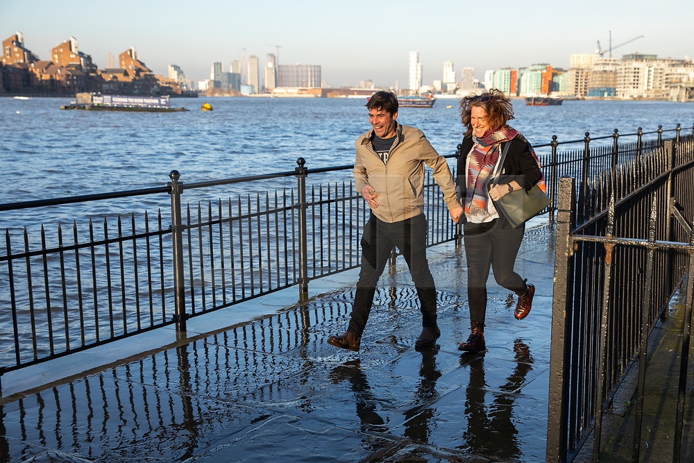 © Licensed to London News Pictures. 22/02/2019. London, UK. A couple run along the Thames Path in Greenwich as an extreme high tide causes the River Thames to flood onto the Thames Path. The weather is also unseasonably warm in the capital, with temperatures set to reach 16 degrees Celsius this weekend. Photo credit : Tom Nicholson/LNP