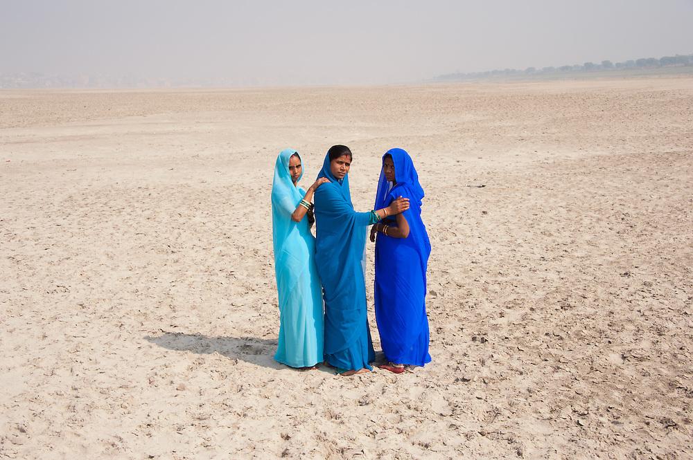 Three women wearing different shades of blue sari's (saree) wallking on the banks of river Ganga, Varanasi (India)