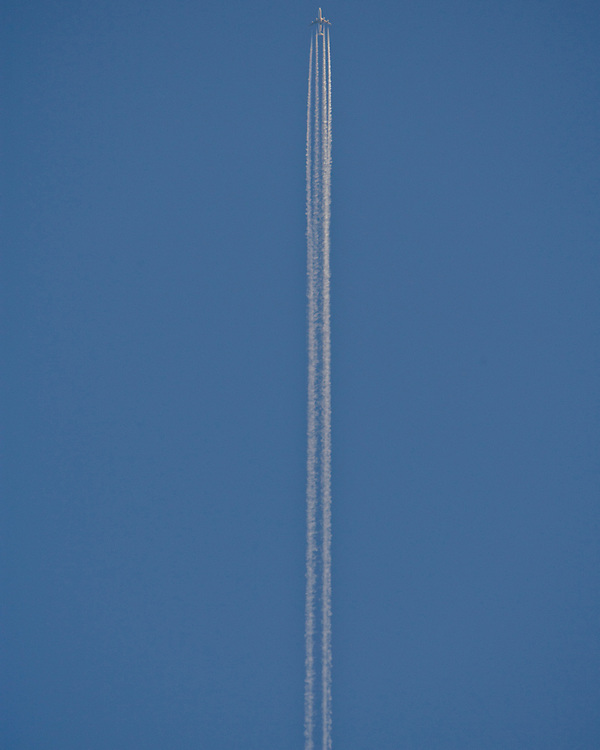 A Jet plane throwing out Jet Stream lines against a blue sky