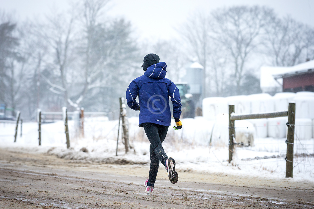 Joanie trains for Boston marathon during spring snow storm at Wolfe Neck Farm in Freeport, Maine, USA