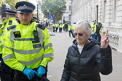 London, UK. 9 October, 2019. A climate activist from Extinction Rebellion gives a victory sign as she is arrested in Whitehall on the third day of International Rebellion protests to demand a government declaration of a climate and ecological emergency, a commitment to halting biodiversity loss and net zero carbon emissions by 2025 and for the government to create and be led by the decisions of a Citizens' Assembly on climate and ecological justice.