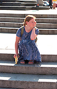 Girl age 20 having a quiet moment sitting on steps with a beer.  Warsaw Poland