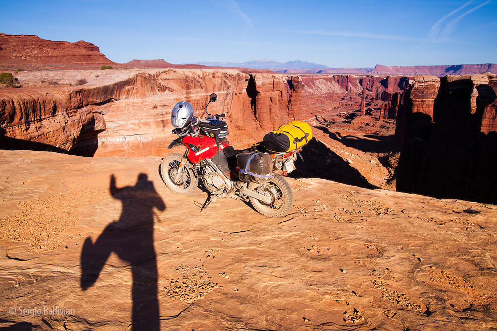 Adventure moto biker and his BMW F650GS parked at White Rim Trail in Canyonlands National Park, near Moab, Utah.