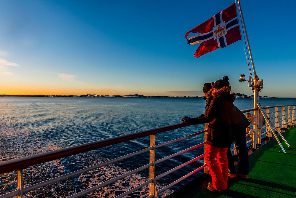 Passenger aboard Hurtigruten ship MS Vesteralen enjoying the scenery on deck , near Alesund, Norway.