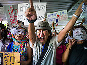 "02 JUNE 2013 - BANGKOK, THAILAND:  An anti-government protester screams as he marches through the skywalk system in Bangkok. The so called White Mask protesters are strong supporters of the Thai monarchy. About 300 people wearing the Guy Fawkes mask popularized by the movie ""V for Vendetta"" and Anonymous, the hackers' group, marched through central Bangkok Sunday demanding the resignation of Prime Minister Yingluck Shinawatra. They claim that Yingluck is acting as a puppet for her brother, former Prime Minister Thaksin Shinawatra, who was deposed by a military coup in 2006 and now lives in exile in Dubai.    PHOTO BY JACK KURTZ"