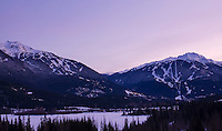 The dual mountains of Whistler and Blackcomb glow against a purple sky in early winter.