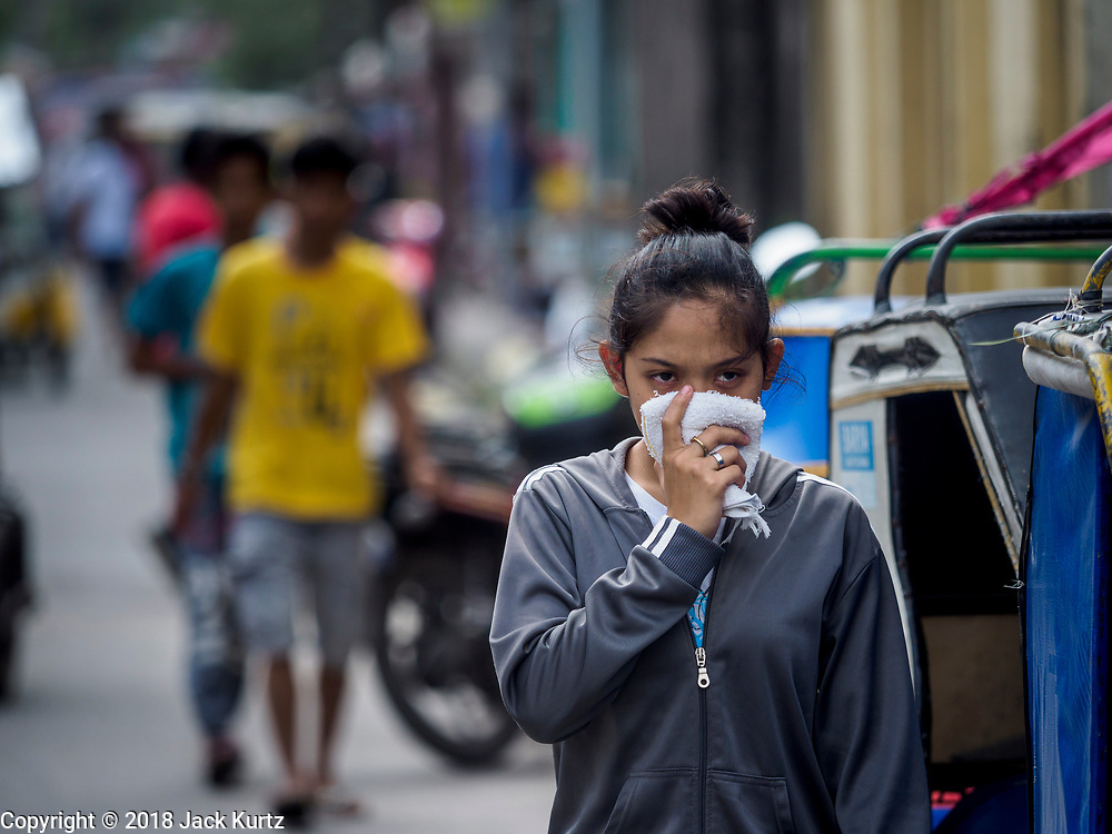 24 JANUARY 2018 - LIGAO, ALBAY, PHILIPPINES: A woman walks down a street in Ligao, covering her mouth and nose during a volcanic ash fall. The Mayon volcano continued to erupt Tuesday night and Wednesday forcing the Albay provincial government to order more evacuations. By Wednesday evening (Philippine time) more than 60,000 people had been evacuated from communities around the volcano to shelters outside of the 8 kilometer danger zone. Additionally, ash falls continued to disrupt life beyond the danger zones. Several airports in the region, including the airport in Legazpi, the busiest airport in the region, are closed indefinitely because of the amount of ash the volcano has thrown into the air.    PHOTO BY JACK KURTZ
