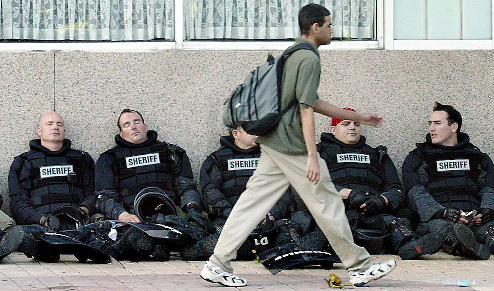 A demonstrator walks by a row of exhausted police after a rally to protest the Free Trade Area of the Americas (FTAA) meetings in  downtown Miami, Florida 20 November 2003. Hundreds of police officers lined the streets and met with hundreds of protesters as they demonstrated and thousands more are expected to converge on Miami during the week to protest the meetings.  EPA/ANDREW GOMBERT