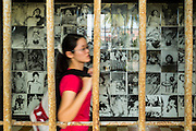 28 JUNE 2013 - PHNOM PENH, CAMBODIA:   A tourist walks past a display of photos of victims of the Khmer Rouge at the Toul Sleng Genocide Museum. The Tuol Sleng Genocide Museum is in Phnom Penh. It is a former high school that was used as the Security Prison 21 (S-21) by the Khmer Rouge from 1975 to 1979. It was used to torture and execute Cambodians and foreigners the Khmer Rouge thought were opposed to the regime.    PHOTO BY JACK KURTZ