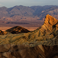 Death Valley, California, USA<br /> Captured in this photo is evidence of a land shaped by several of the earth&rsquo;s most transformational forces: water erosion, wind erosion, volcanic, and plate tectonics like basin/range extension and earthquake. <br /> Morning light at Zabriskie Point in Death Valley National Park. The sun's light had raced across the valley floor and was gradually making its way up the Amargosa Range on the east side of the valley. Manly Beacon, sticking up, is able to catch those rays before the surrounding badlands formations.  Death Valley is a world of extremes. As one of the hottest and driest places on the planet, it supports a staggering amount of wildlife, and despite the lack of water, some of its most prominent landscapes are the result of water erosion. <br /> Canon EOS 6D; Canon EF 70-200mm f/2.8L IS II USM; Gitzo tripod, RRS Ballhead<br /> 1/125s; f/8; 102mm; ISO 100<br /> Post Processing done using Lightroom 5.7.1