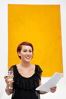 Smiling young woman in front of yellow wall painting