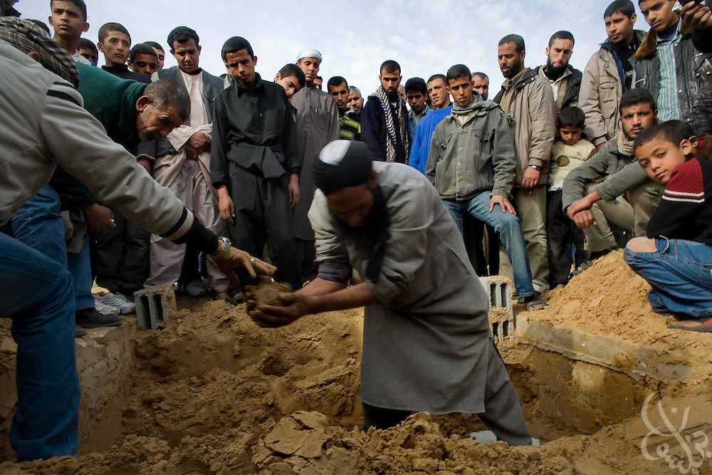 Palestinian men bury a 12 year old boy killed during an Israeli airstrike at a January 16, 2009 funeral  in Rafah Gaza. The Israeli Defense Forces claim their sustained campaign has significantly degraded smuggling tunnels along  the corridor and the damaged the ability of HAMAS to smuggle weapons and cash into the Strip, but it has also killed civilians unlucky to have been still in the vicinity of targeted neighborhoods. (photo by Scott Nelson, World Picture Network for the New York Times)