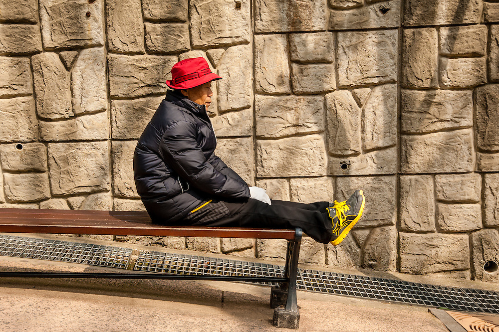 A man rests on a bench at Busan Grand Children's Park in Busan, South Korea.