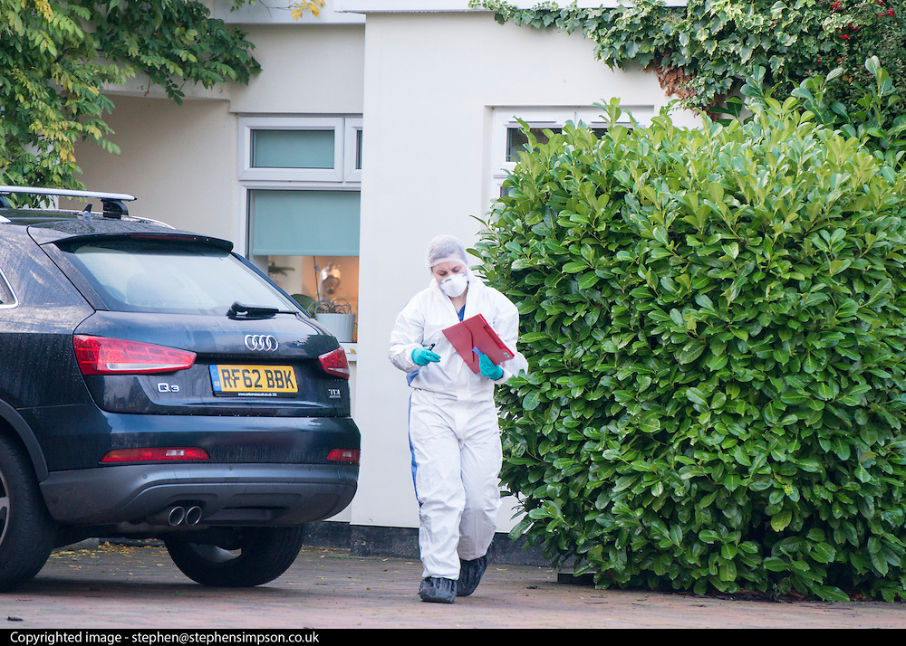 © Licensed to London News Pictures. 27/11/2014. Fetcham, UK. A forensic officer leaves the house.  A manhunt is under way across two counties after a man and woman were found stabbed to death in Surrey. The bodies were found at a house in Fetcham, near Leatherhead, after Surrey Police were alerted in the early hours.. Photo credit : Stephen Simpson/LNP