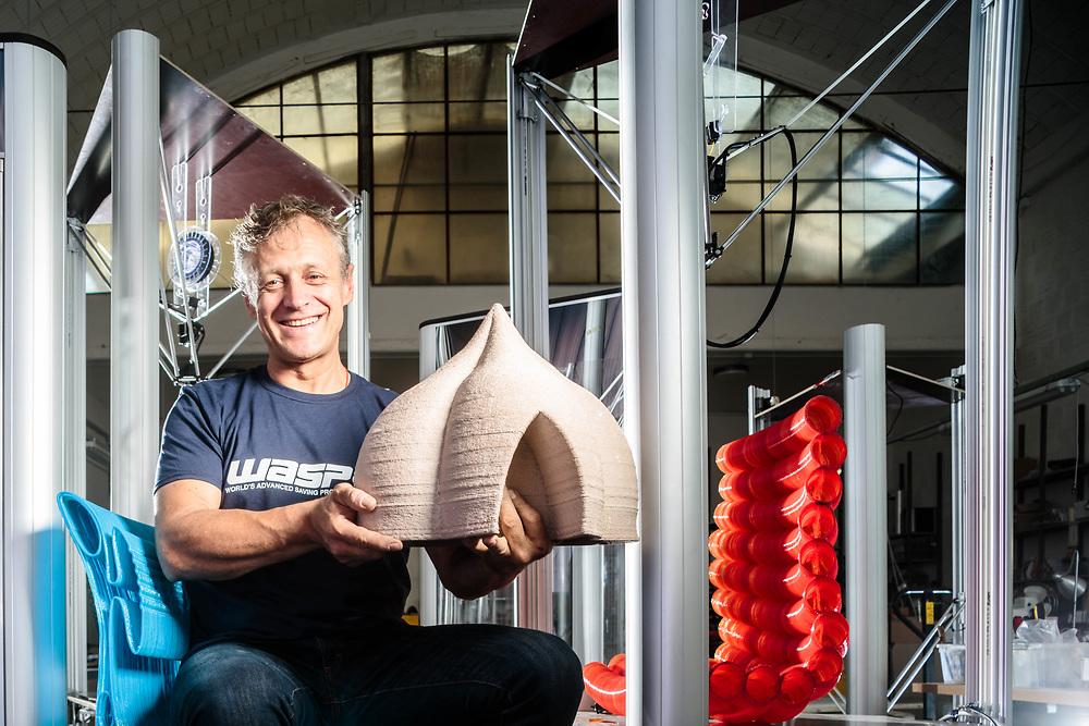 """08 JUN 2016 - Massa Lombarda (RA) - """"CSP"""", WASProject, stampanti 3D: Massimo Moretti, fondatore, tra alcune stampanti, due sedie stampate e il modellino di una casa."""