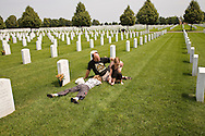 Young caucasian male by a grave marker at a military cemetary
